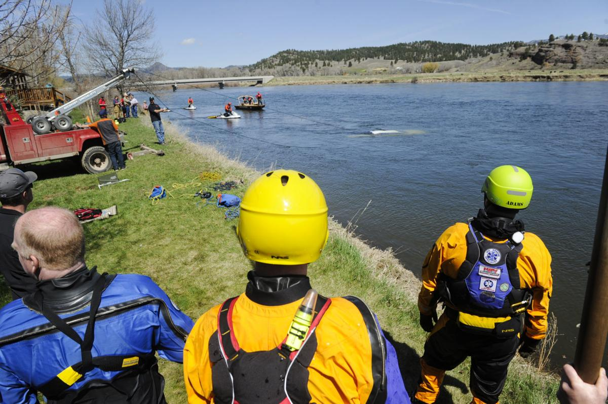 Search and rescue divers watch as a truck is removed from the Missouri River near Craig Monday.