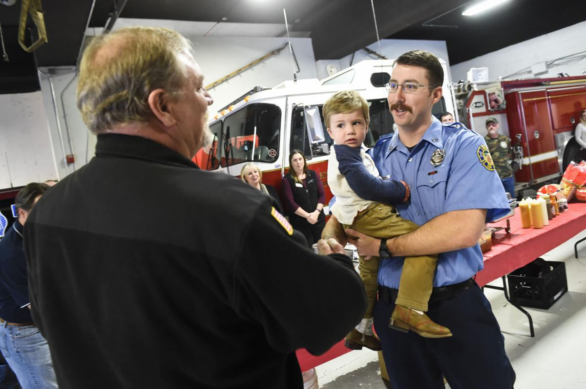 Robbie Bennett with his son, Henry, in arms accepts the Helena Firefighter of the Year award presented byt the Helena Exchange Club Thursday afternoon at Helena Fire Station Number 1.