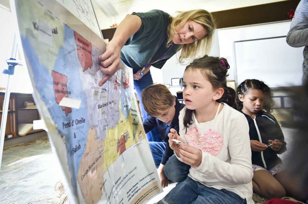 Montessori teacher Katy Wright, center, helps her student Lexi Holland