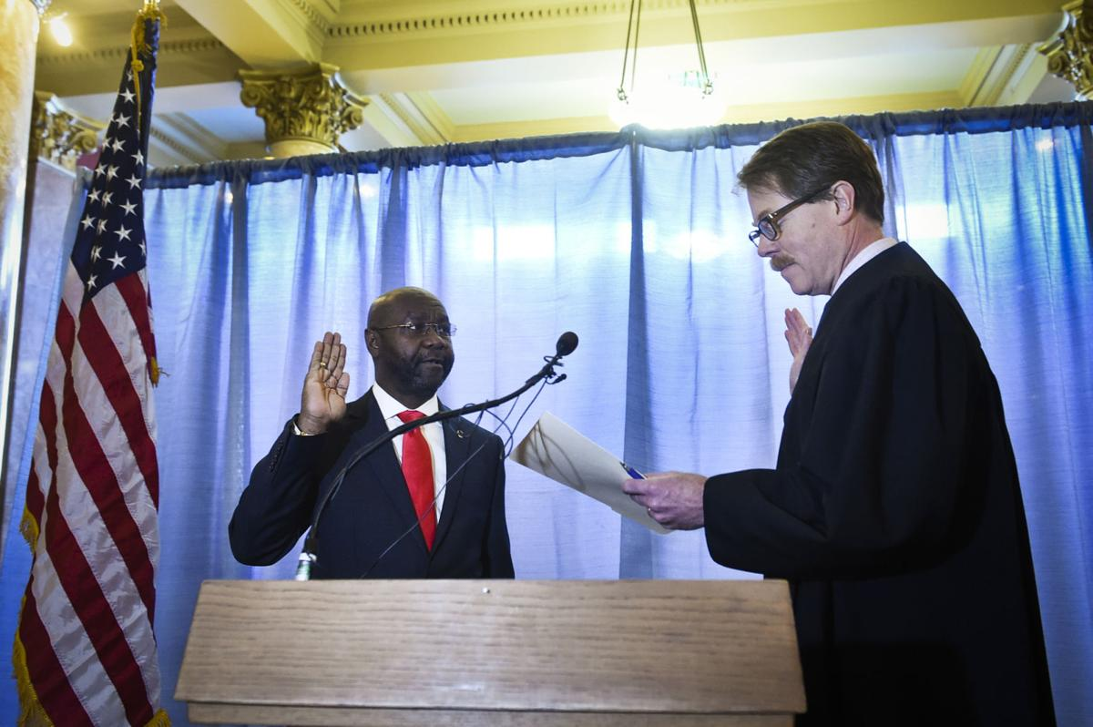 Helena's new mayor Wilmot Collins, left, is sworn into office Tuesday morning by Judge Mike Menahan in the Capitol Rotunda.