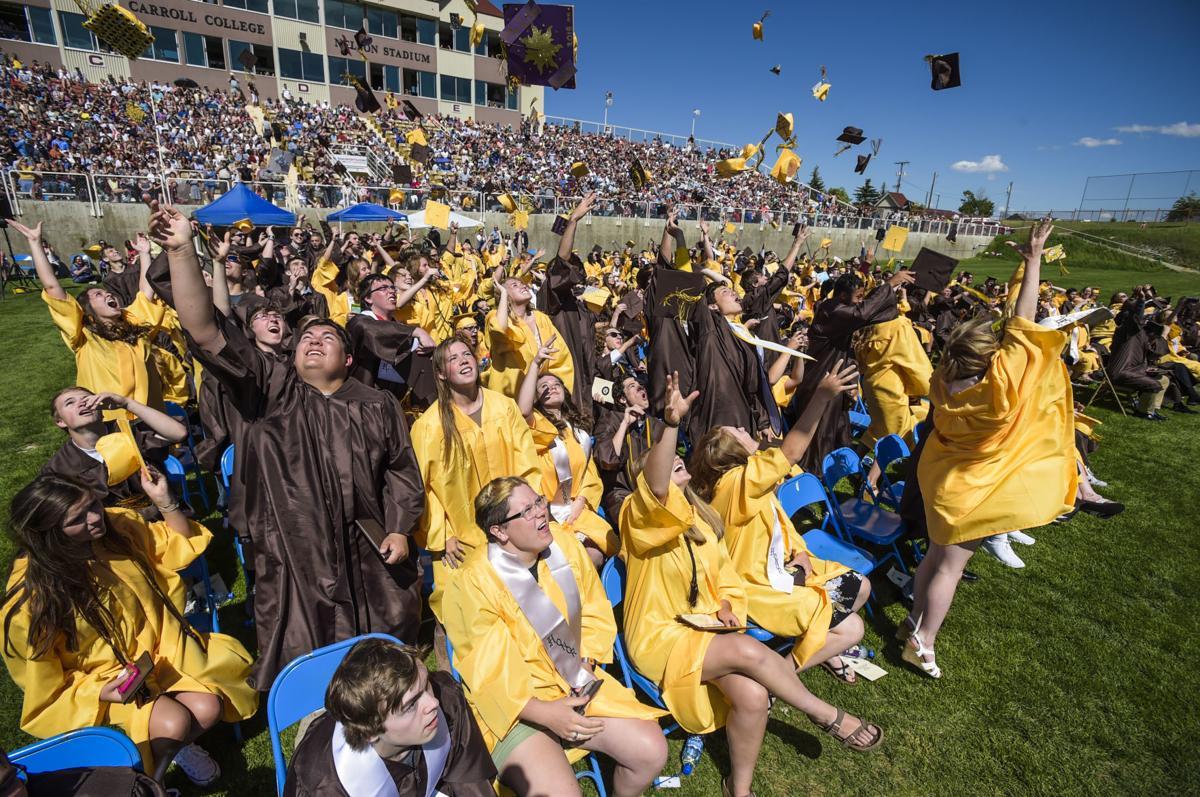 Capital High School graduates toss their caps