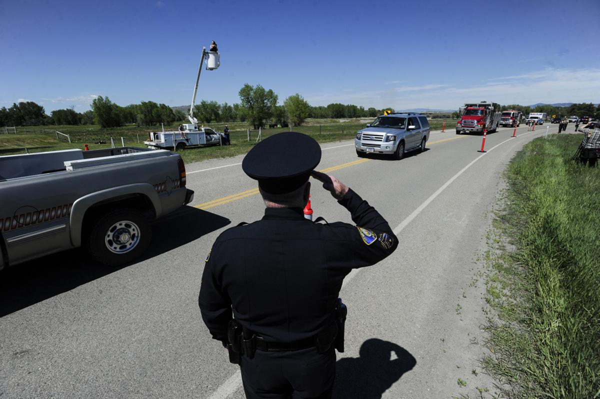 A law enforcement officer salutes as the procession of deputy Mason Moore rolls into Three Forks Tuesday afternoon.