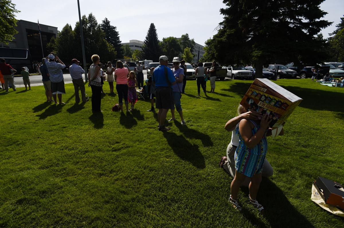 A few hundred people gather outside the Montana Historical Society Monday morning to view the solar eclipse.