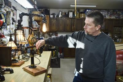 Don Reich shows off one of his steampunk lamps in his Helena shop recently.