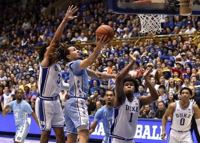 In this file image, Cole Anthony #2 of the North Carolina Tar Heels drives between Tre Jones #3 and Vernon Carey Jr. #1 of the Duke Blue Devils during the second half of their game at Cameron Indoor Stadium on March 7, 2020 in Durham, North Carolina.