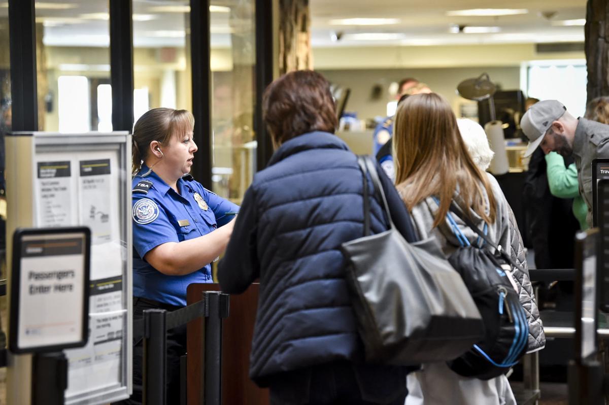 A TSA worker checks passengers through security