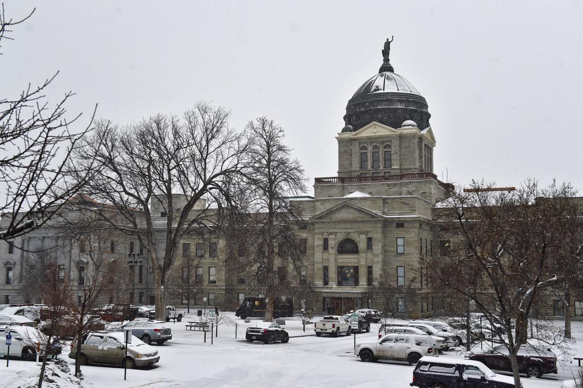Snow falls on the Montana State Capitol Thursday.