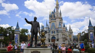 Guests watch a show near a statue of Walt Disney and Mickey Mouse at Walt Disney World in Lake Buena Vista, Fla.