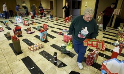 Volunteer Sharon Nolte helps sort gifts at Our Lady of Lourdes Church to distribute during a Christmas party for residents at Decatur Manor Healthcare.