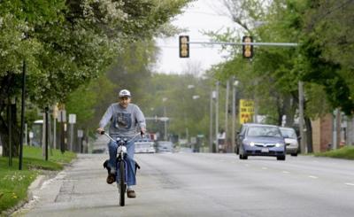 b80a8abb0 Scott Walden rides a motorized bicycle down a Decatur street. Herald    Review Mark Roberts Mark Roberts
