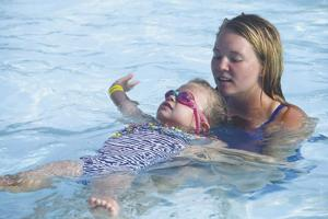 <p>Schlitterbahn Waterparks & Resorts instructor Ma Kenzi Glass supports 4-year-old Addyson Schulz, of New Braunfels, as she stretches out her arms and tries to float on her back while participating in Thursday's World's Largest Swim Lesson. Schlitterbahn and Colin's Hope partnered to sponsor the local portion of the worldwide event created to spread the word that swimming lessons save lives.</p>