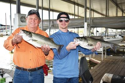 Two Lukes holding stripers