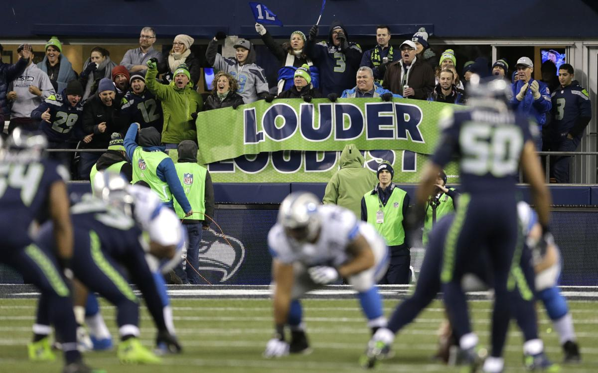 Seattle seahawks fans yell behind a banner that reads louder during the first half of an nfc wild card playoff game against the detroit lions on jan