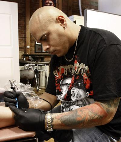 b5b2f4854 Tattoo artist Mike Rivera works on a piece for a client at his River Street  shop.