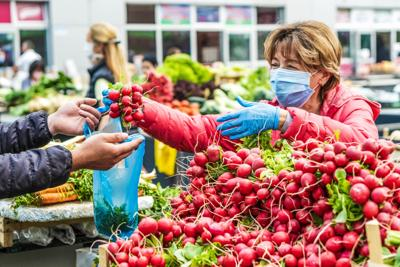 Farmers market vendor wears mask and gloves