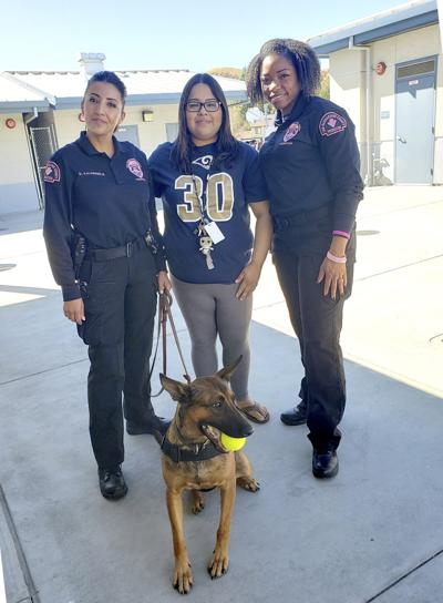 K-9 Izzy poses with (from left to right) Officer Denise Valenzuela, Holcomb counselor Antoinette Bueno and Officer Dominique Bright
