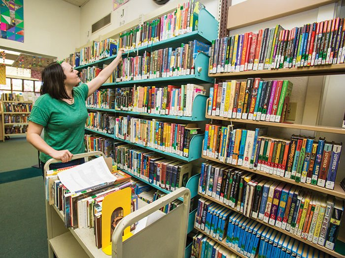 Library Assistant shelving books in the library