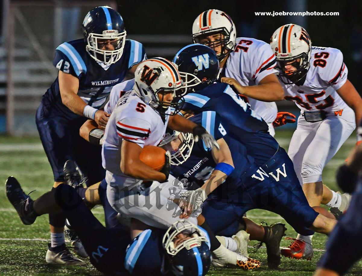 WHS Football team's defensive line tackles a Woburn ball carrier