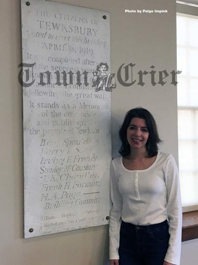 Maria Zaroulis stands next to the marble tablet in town hall