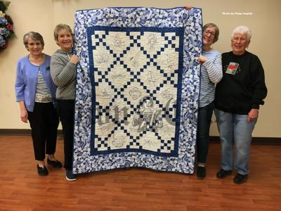 Tewksbury Piecemakers Quilt Guild members show off a 50th anniversary quilt