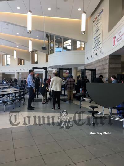 Students pass through metal detectors