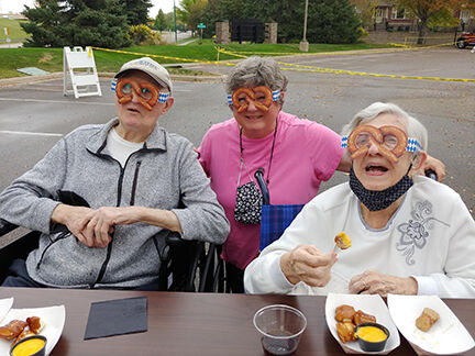 From left: Don Wells, Susan Newville, and Helen Wells got a kick out of the pretzel glasses available to festers.
