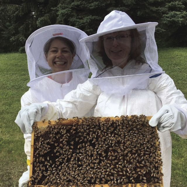 Dawn-Johnson-doing-a-hive-check-with-a-Jessica-Serbin-2 bees.jpg
