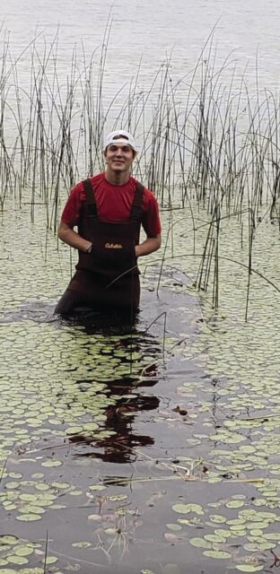 Luckasz in waders ready to put posts in water to support dock.JPG