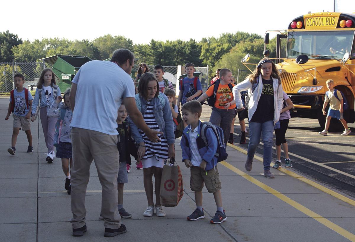Staff members greet students