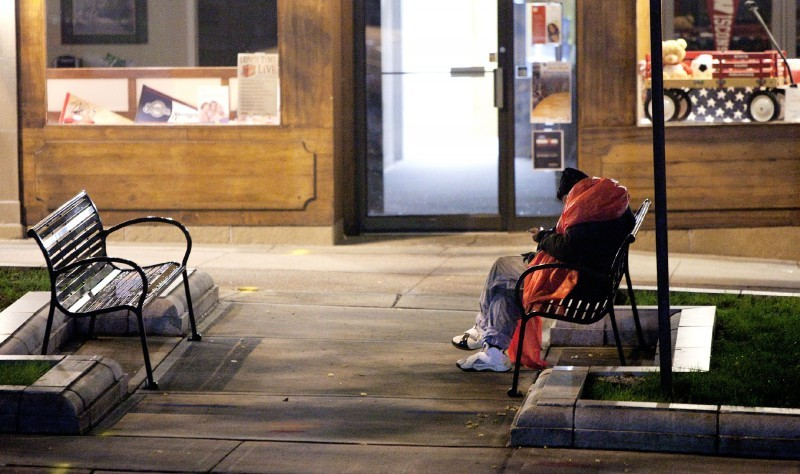 Homeless man sleeping on bench in Madison file photo