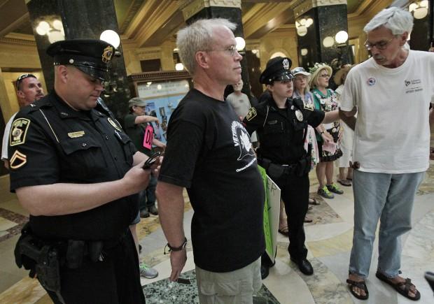 Police officer arrests singer at Capitol protest