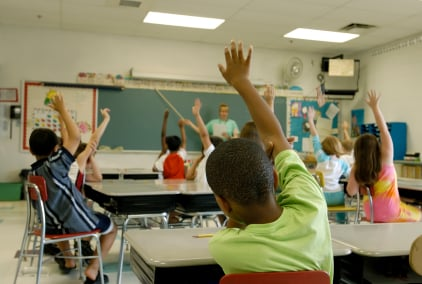 kids in classroom raising hands iStock photo