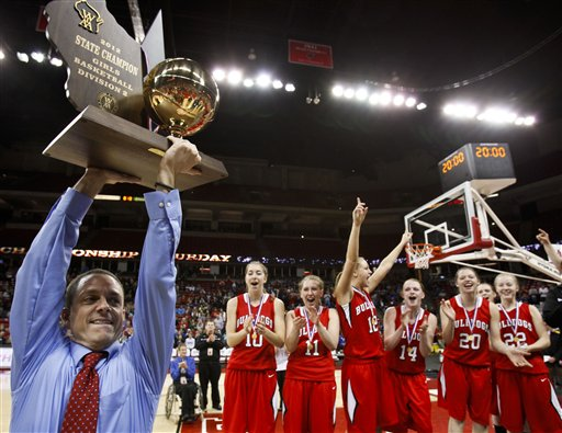 New London coach Troy Krause holds up the Division 2 championship trophy