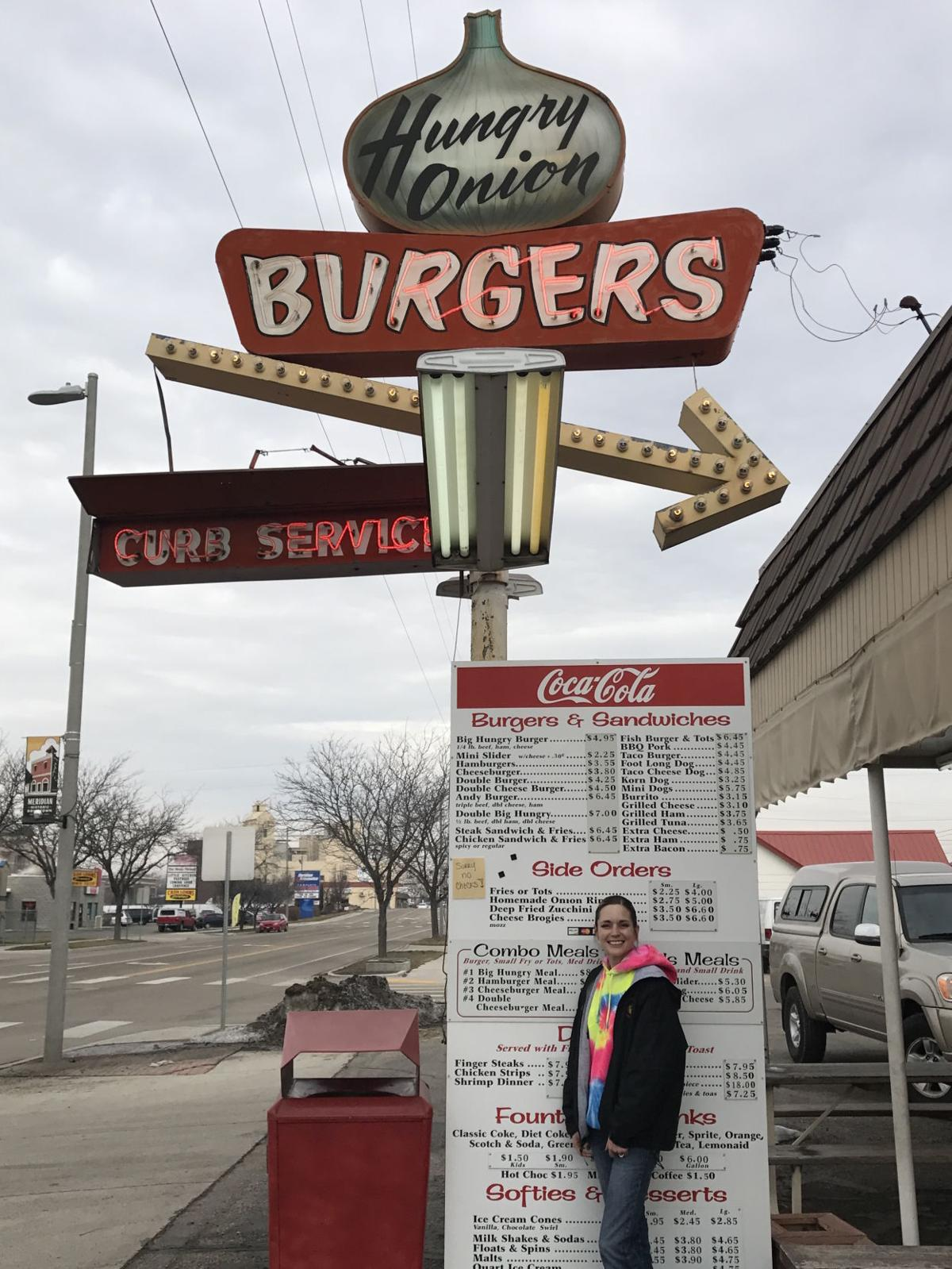 Hungry Onion Drive-Inn manager Brooke Robbins poses in front of the restaurant's 54-year-old sign.