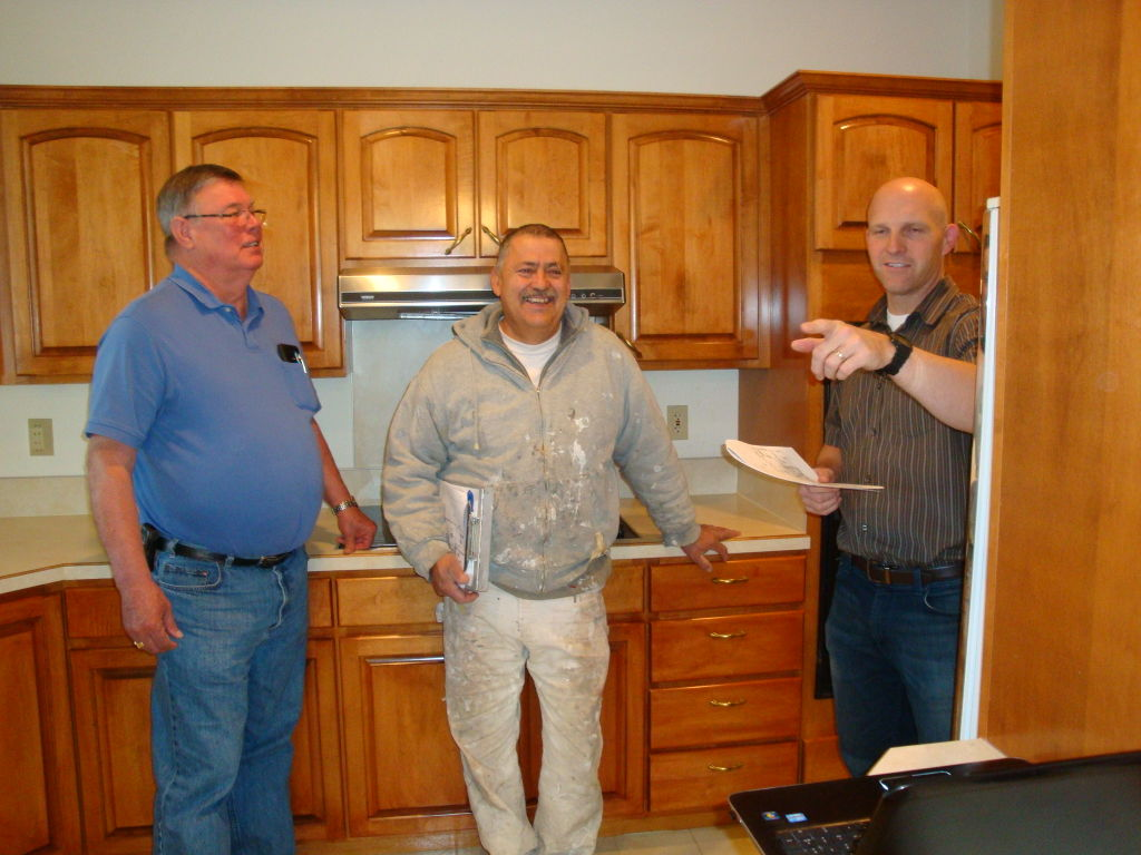 Builder and Idaho Army National Guard Lieutenant Mike Hill, right, discusses details of remodel job with Eagle homeowner, Donald Hilton, left, and painter Gary Bell.
