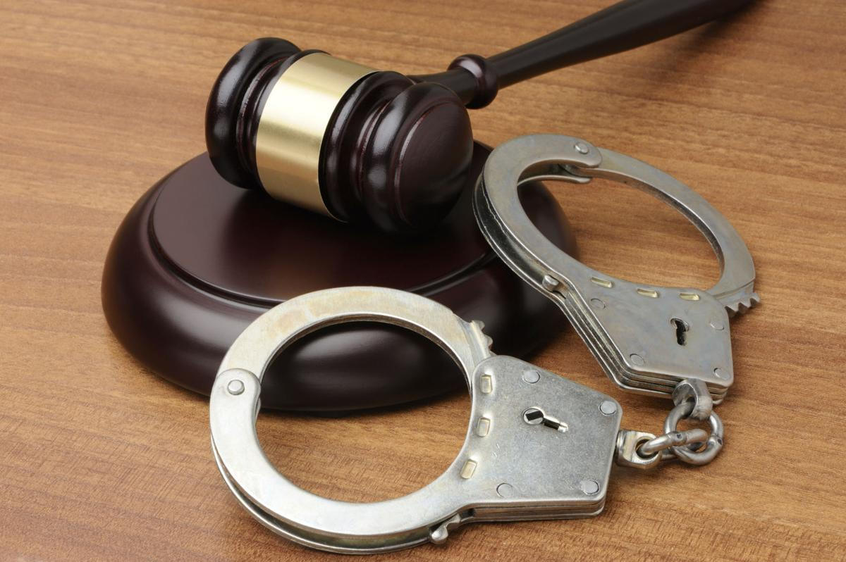 Handcuffs with gavel on a wood background