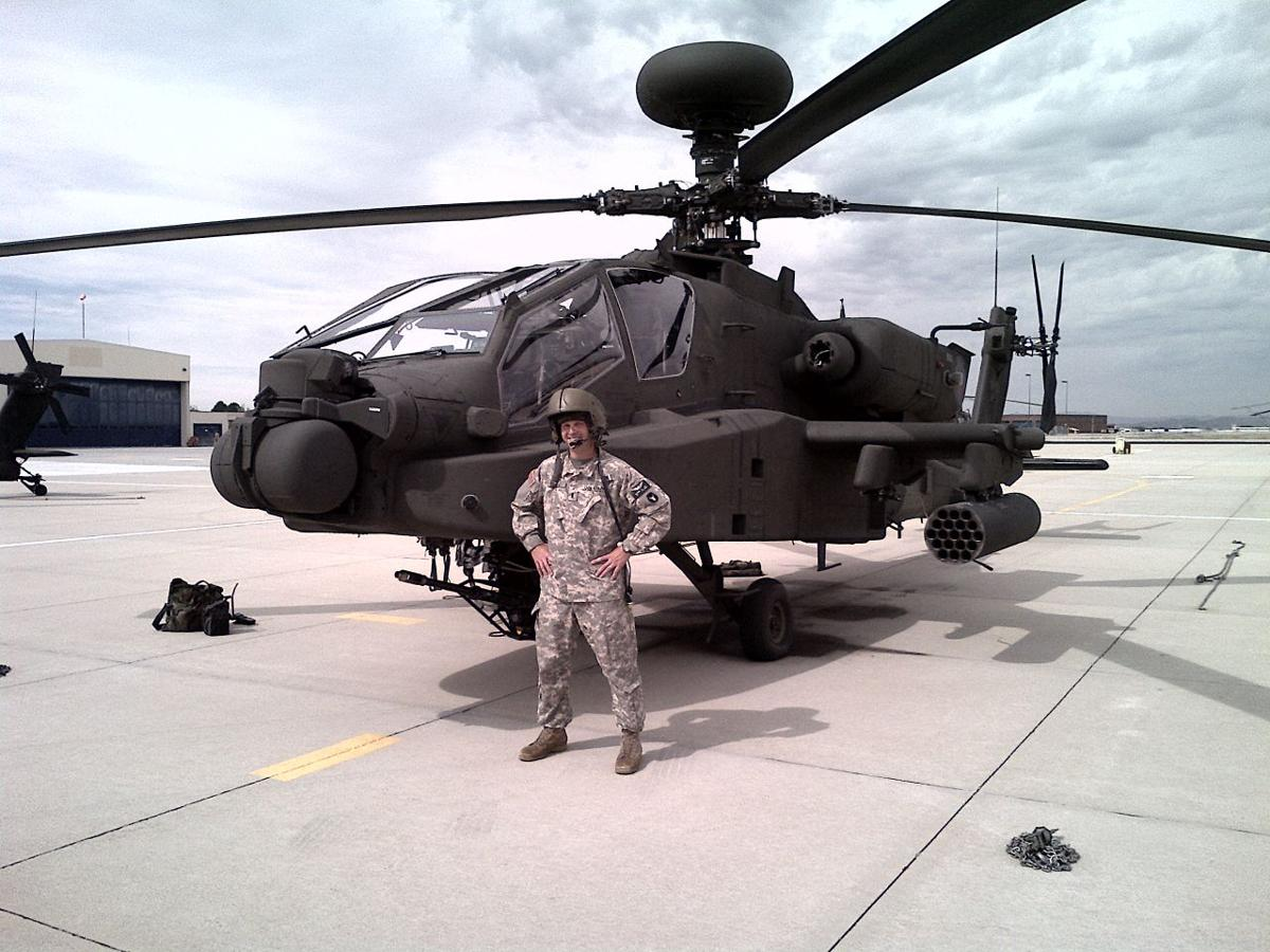 Lt. Mike Hill stands in front of the heavily armed Apache attack helicopter at Gowen Field in Boise.