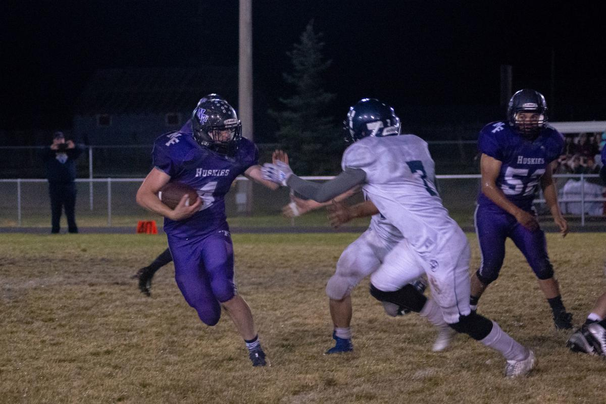 North Fremont's Oberhansley reaches out to stiff arm a West Jefferson defender.