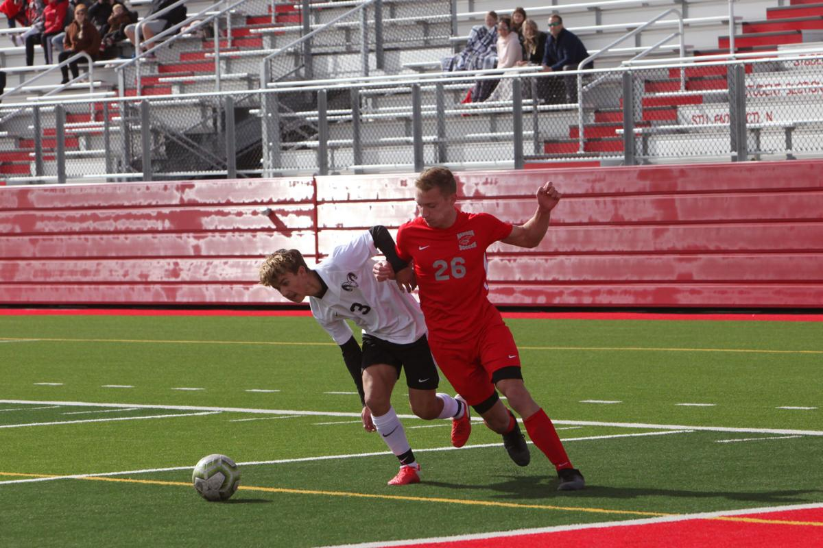 Madison's Mark Huish battles a Highland defender for control of the ball.
