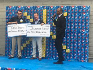 <p>The Imperial Beach Senior Center and the City of Imperial Beach received checks for $1,000 from Walmart during the store's grand reopening. Assistant Manager Yasir Gallardo, left, and Imperial Beach Councilman Mark West held the checks while General Manager Mytrell Foreman, right, spoke on the microphone.</p>