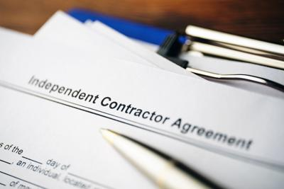 Legal Document Independent Contractor Agreement On Paper Close Up.