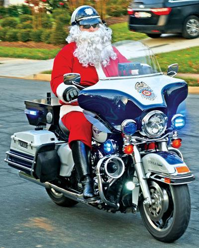 Santa on police motorcycle collects toys