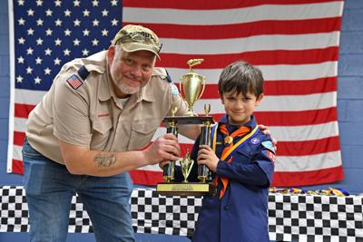 Pinewood Derby brings out Scouts' creativityPHOTO BY IAN Chini   Cub Scout Pack 550 Leader Robert Van Nostrand presents Jacob Grimes with this year's Pinewood Derby Trophy.
