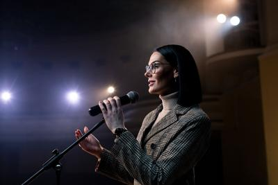 Portrait Of Women Speaking Through A Microphone In Dark Conference Hall. Woman Talks Into Microphone