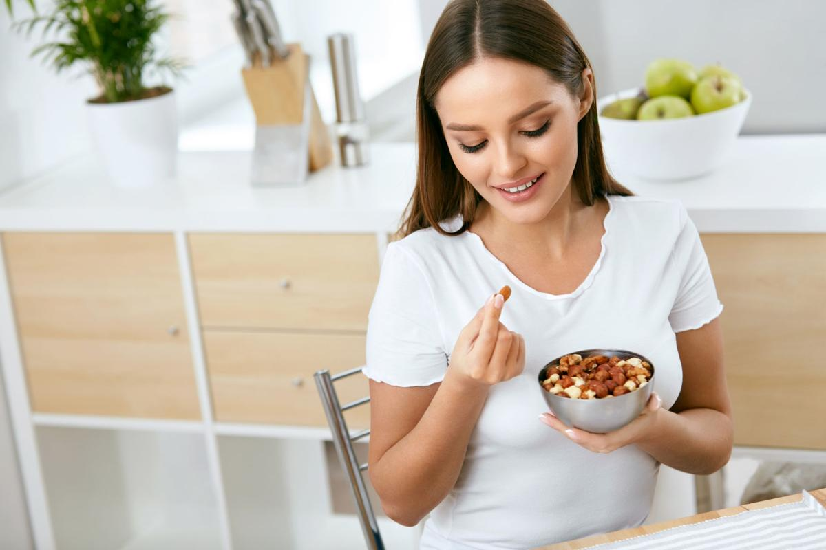 Healthy Food. Happy Woman Eating Nuts