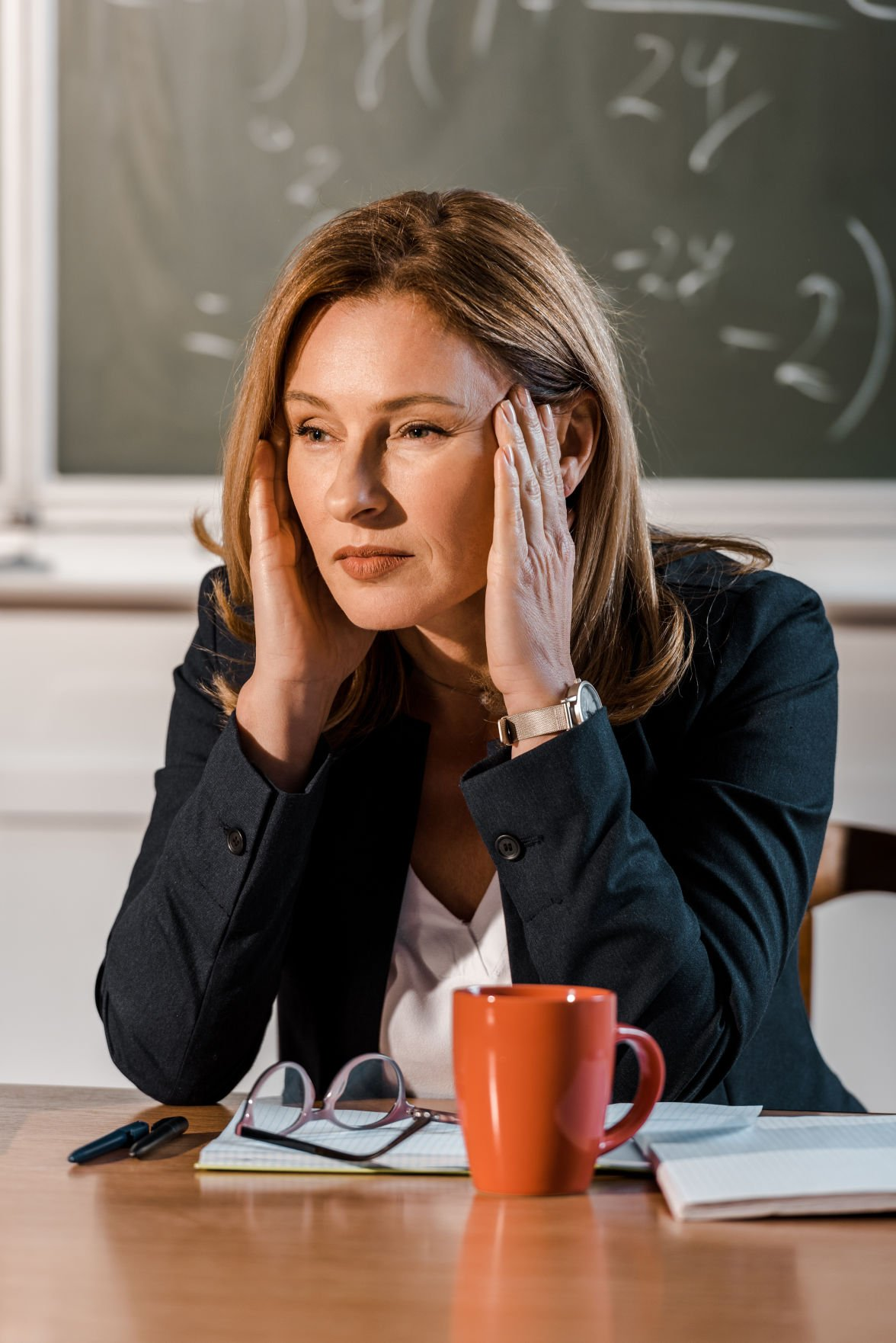 female teacher sitting at desk with hands on head and having headache in class