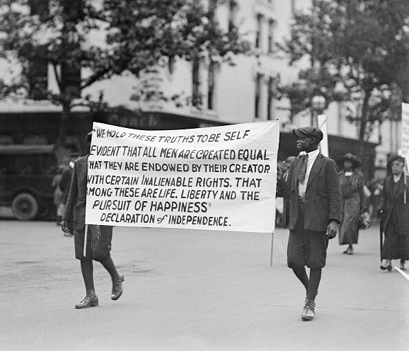 lynching African-American ethnicity carrying marching protester parade four people Washington DC banner capital