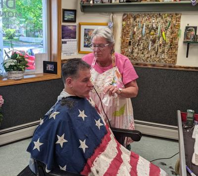 Sylvia Short puts the finishing touches on a customer at the new location of her barbershop