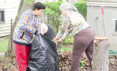 Volunteers clean the grounds of 626 W. Buffalo St. Right: The exterior of 626 W. Buffalo St.