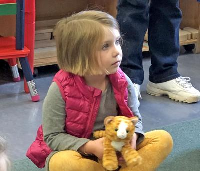 A four-year-old student in Groton's universal pre-k program listens to Izzy's Day at Schoolbeing read out loud while holding an Izzy plushy.